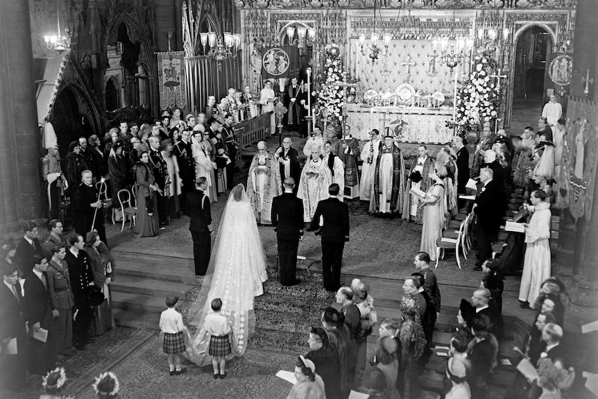 A black and white still of Princess Elizabeth and Philip at the altar of Westminster Abbey.