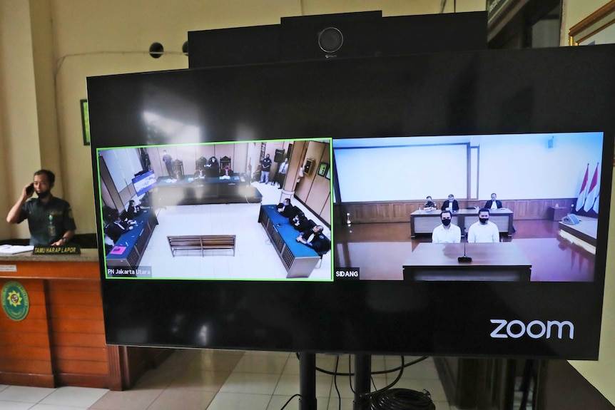 A security officer talks on his mobile phone behind a screen showing the two defendants.