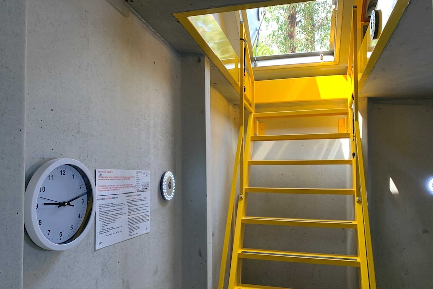 Yellow stairs down to a cement fire bunker, which has a clock on the wall.