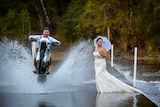 man doing wheelie on dirt bike and splashing woman with water