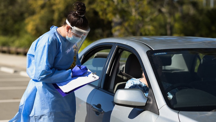 Health worker writes on paperwork with a motorist at a COVID drive-through testing site Brisbane