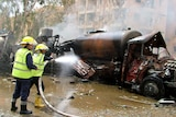 Syrian firefighters douse a burning truck at the site of the blast.