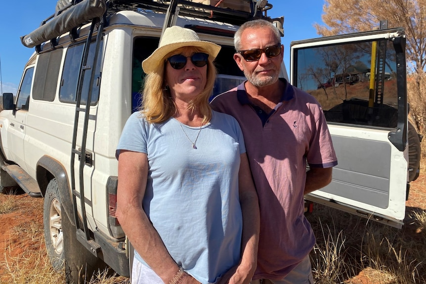 A couple stand in front of a 4WD vehicle in the Central Australian outback.