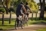 Two men ride bikes along a cement path.