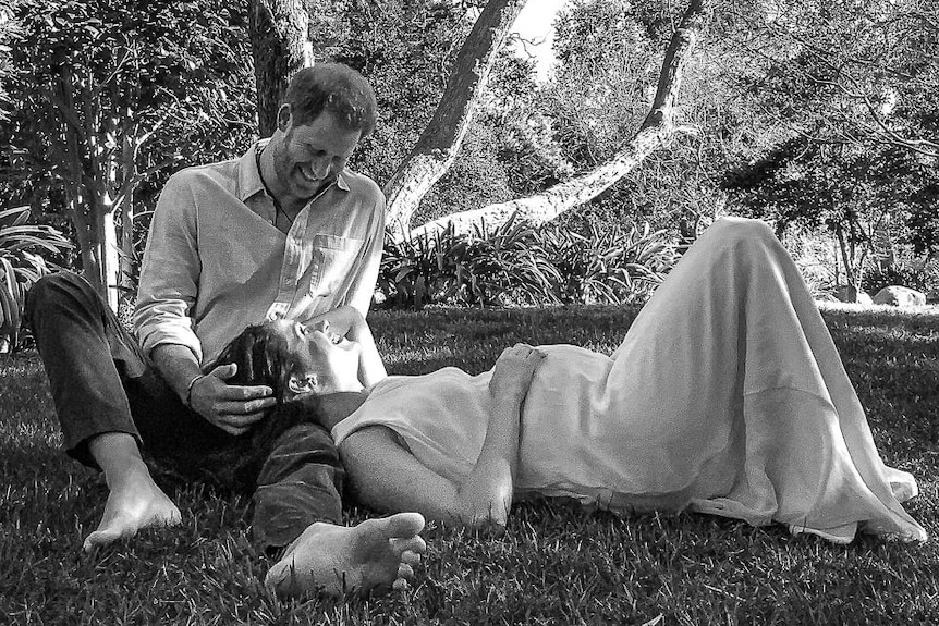 A photo of Harry sitting on the grass with Meghan looking pregnant and her head laying on Harry's lap.