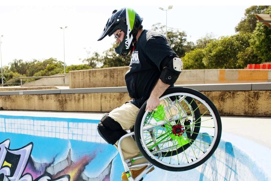 A man in a wheelchair is seen preparing to go down a dip in a skate park. He wears a helmet and knee pads.