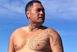Deportee Ko Haapu standing beside the beach.