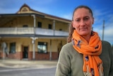 A woman standing outside with a historic pub in the background.