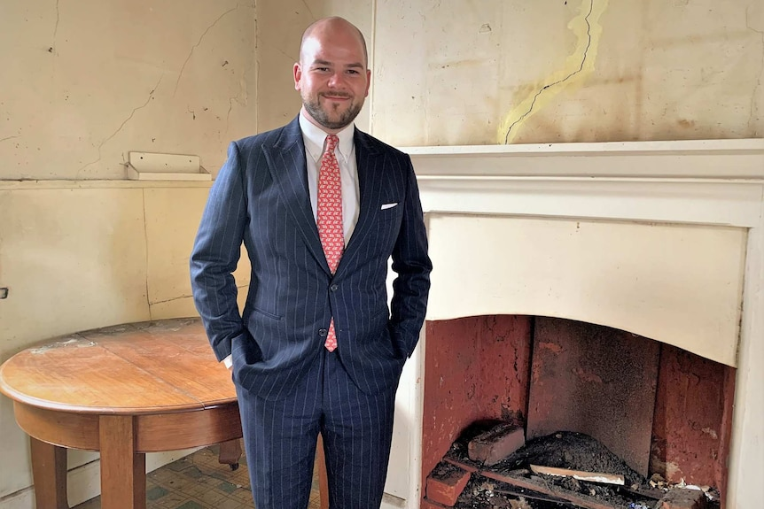 Real estate agent Brad Stephens stands in front of a fire place and table in a run down West Hobart property.