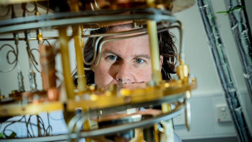 A quantum physicist looks out from behind an isotope.