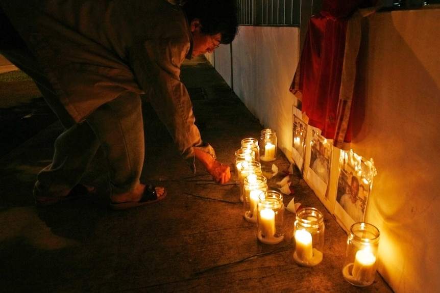 A man lights candles outside a building