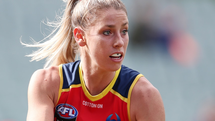 AFLW player with the ball in her hands during a match