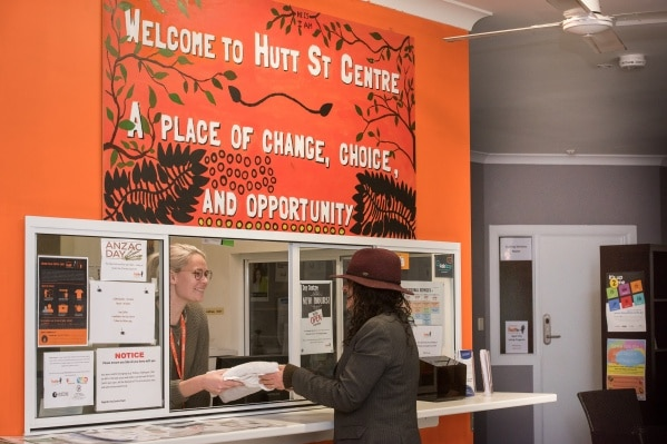 A client in a hat speaks to a woman at reception at the Hutt Street homeless centre in Adelaide