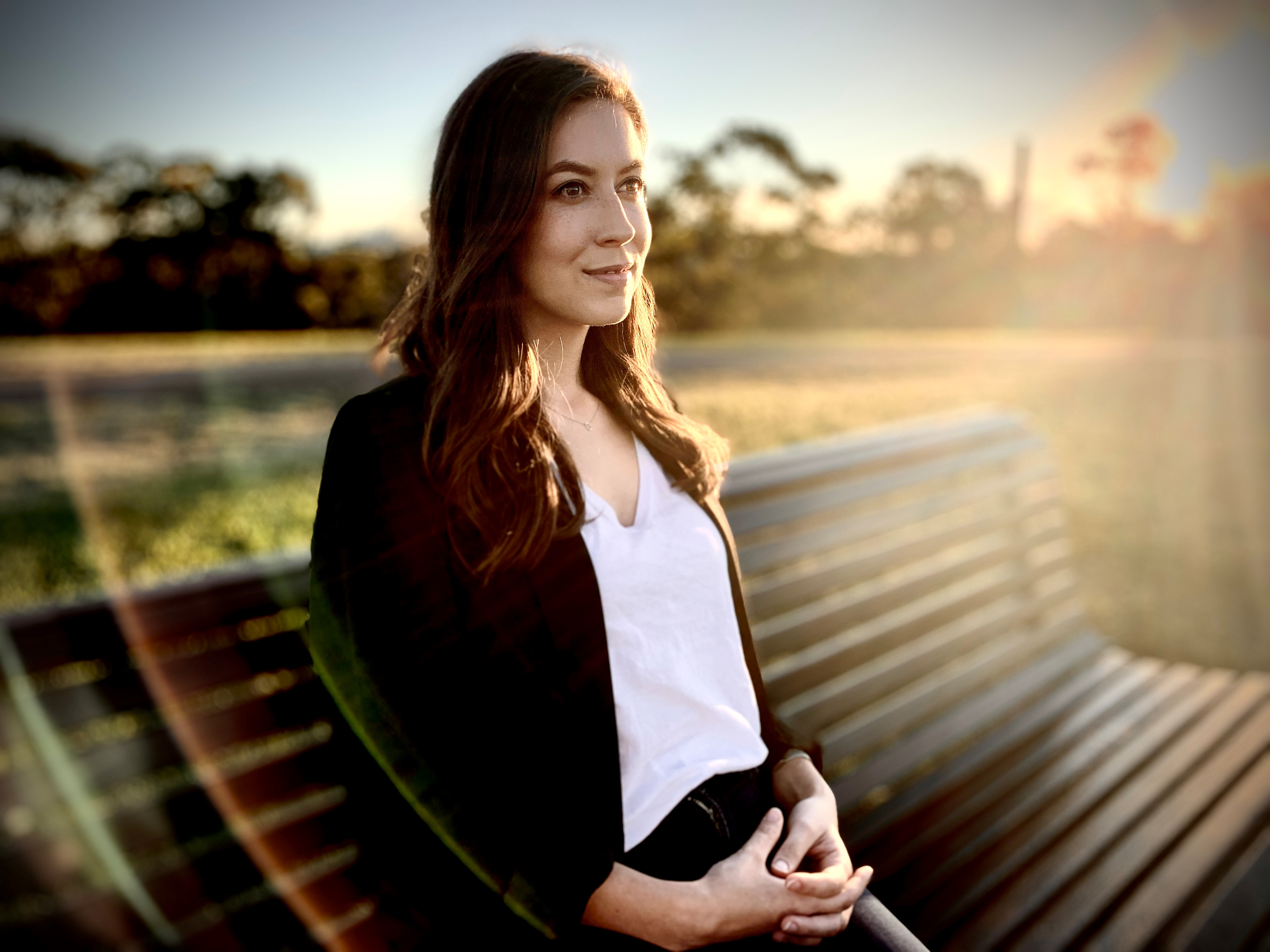 Sharlie Raymond sits on a park bench and looks into the distance