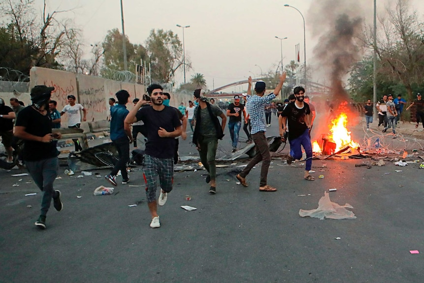 Iraqi protesters run along street past a small fire in Basra