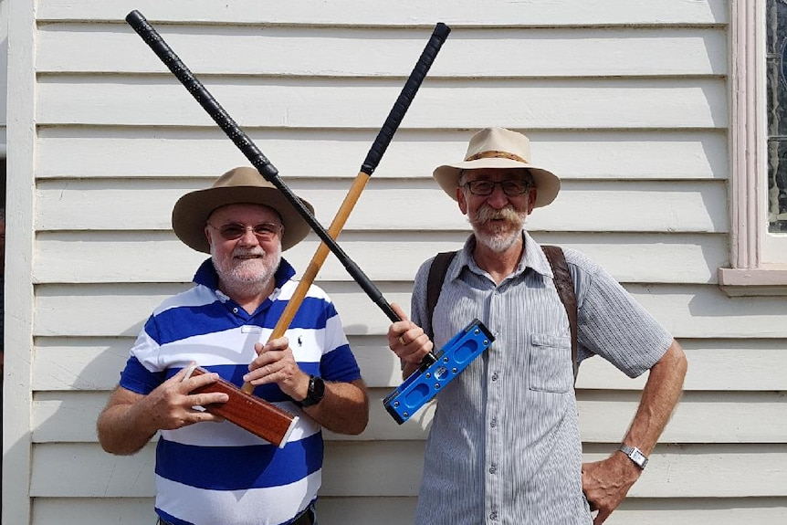 Two croquet members posing with croquet mallets.