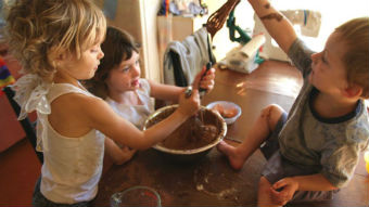 Children play with cake mix in a kitchen.