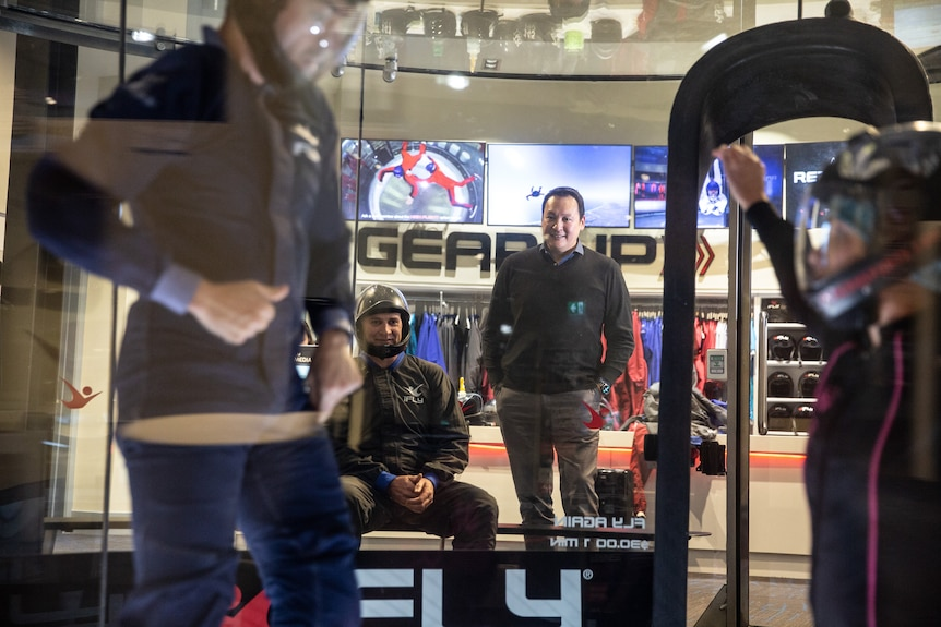 A man watches on as people stand inside a controlled indoor skydiving centre