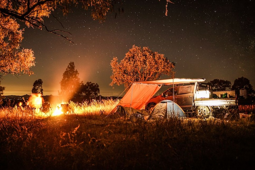 Stunning photo of a campsite under the stars with a glowing camp fire.