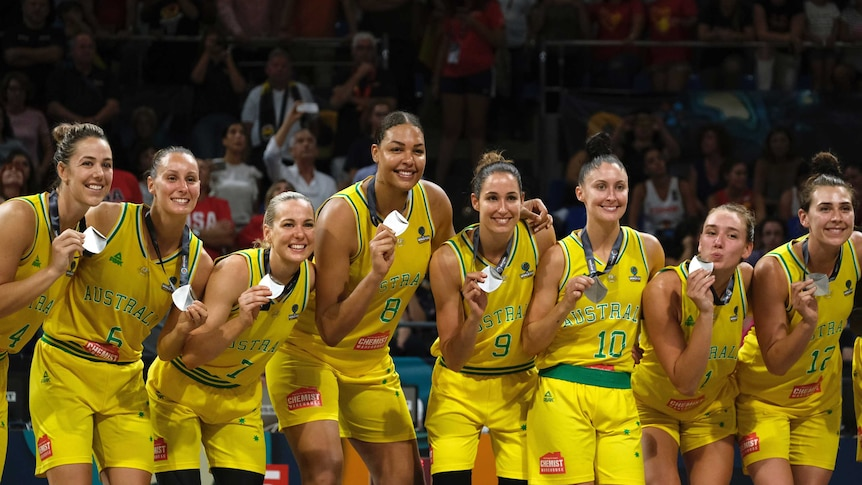 Women wearing yellow singlets stand in a line holding silver medals while smiling.