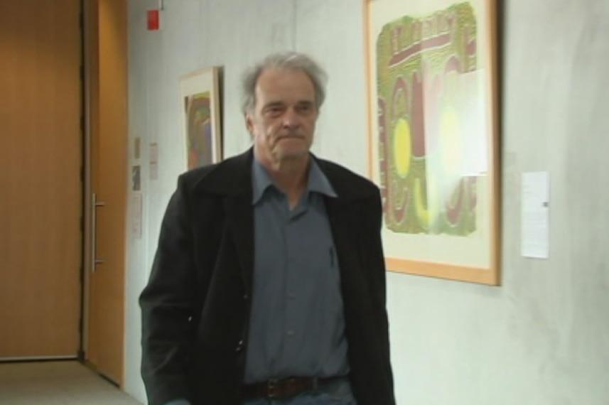 Patrick Venaille walks down a corridor