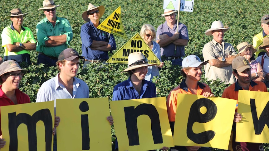 Young farmers stand in a cotton field holding up small signs spelling out '#WrongMineWrongPlace'.