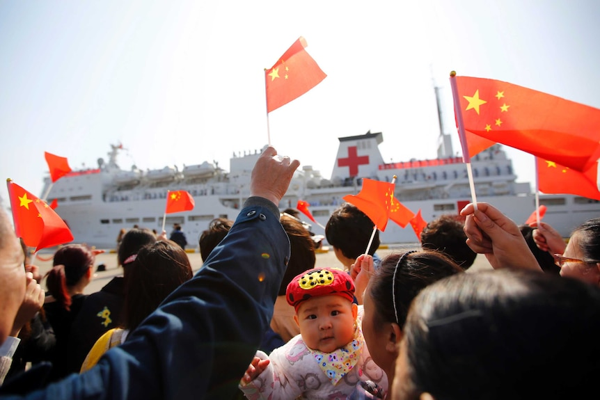 A crowd of people on the dock wave Chinese flags as they bid farewell to the Peace Ark ship.