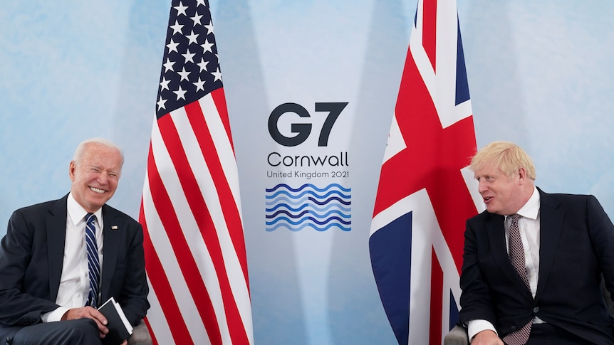 U.S. President Joe Biden laughs while speaking with Britain's Prime Minister at G7 summit.