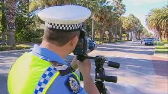 There are few cars on Riverside Drive as a police officer points a speed camera at traffic