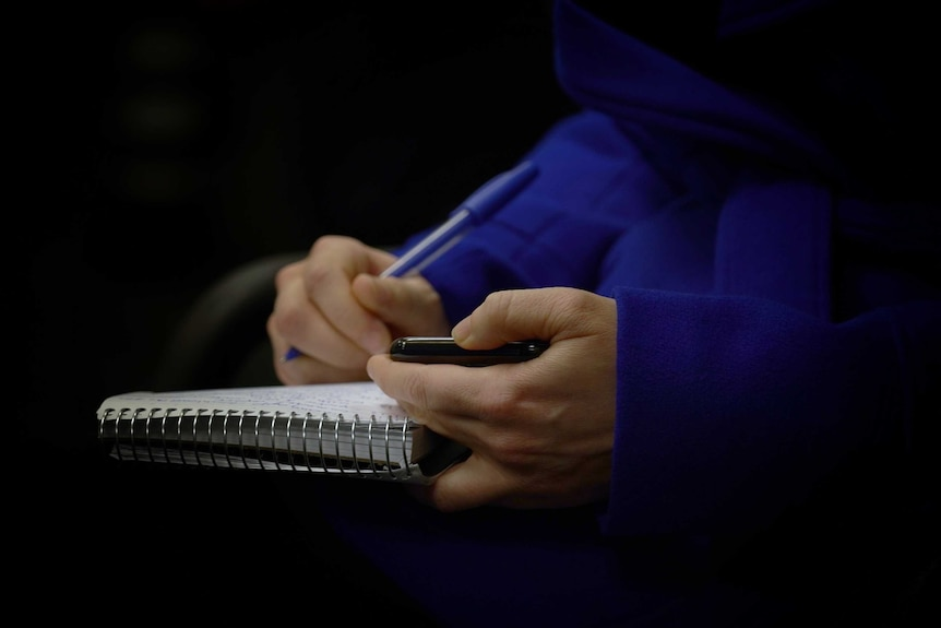 Close up of reporter's hands holding phone and writing notes in notebook.