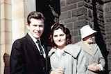 Maria James stands with her husband John outside a building.