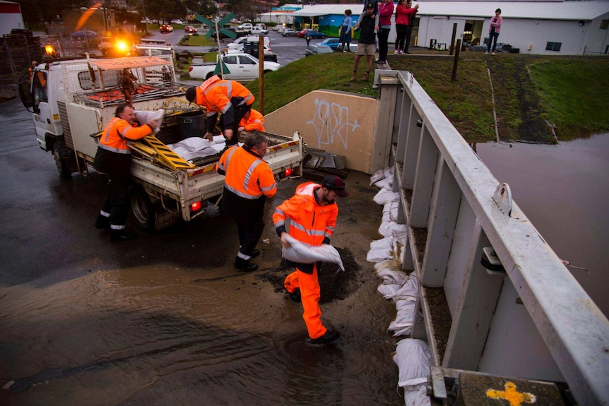 Council workers lay sand bags against floodgates in Launceston