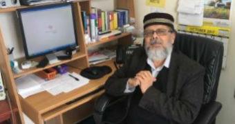 Dr Amjad Hafizullah sitting at his desk.
