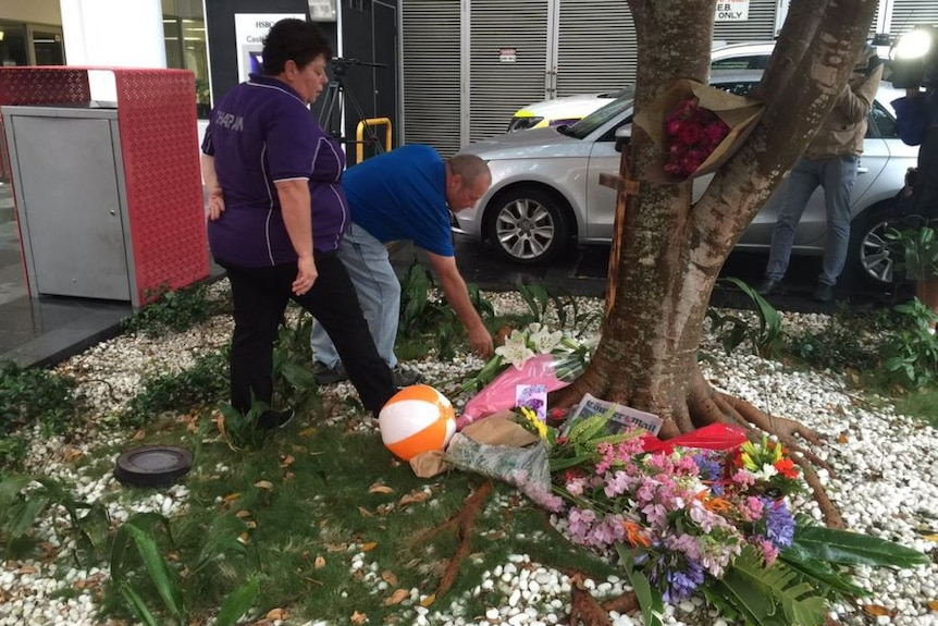 Mourners lay flowers at a vigil.