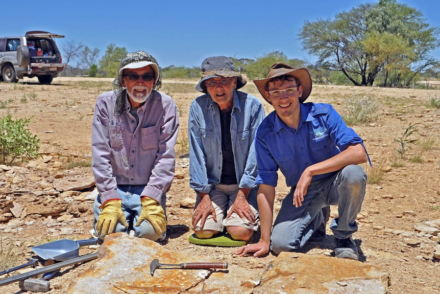 Dr Patrick Smith and volunteers Gary and Barbara Flewelling kneel over sight where rare lizardfish fossil was discovered.