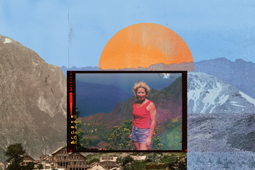 A woman in tank to and shorts stands smiling in sun on mountain side near water.