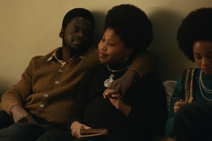Actors Daniel Kaluuya & Dominique Fishback sitting in a loungeroom, arms around eachother, in film Judas and the Black Messiah