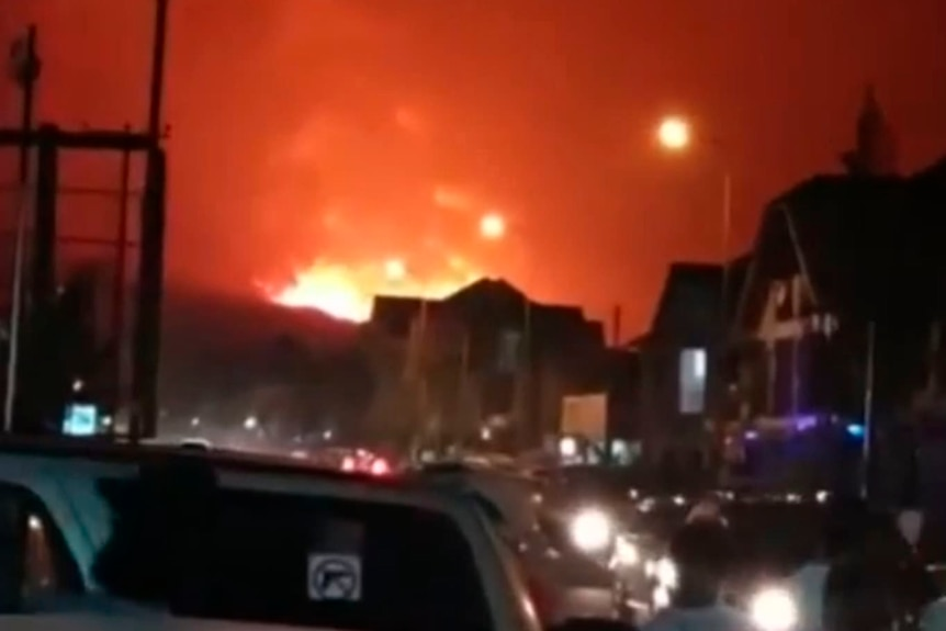 Traffic is stopped in the street and people watch as a volcano erupts behind a city in the night.