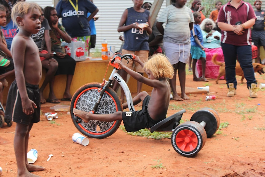 small child riding a tricycle