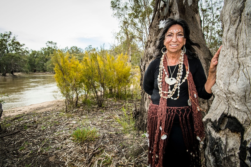 A woman stands next to a tree with a large river in the background.