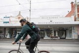 A cyclist rides past a store named Belle Mariee Bridal