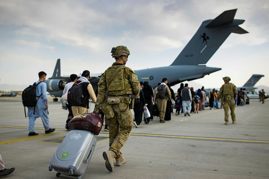 A soldier with a suitcase at an airport in a line of Afghan people.