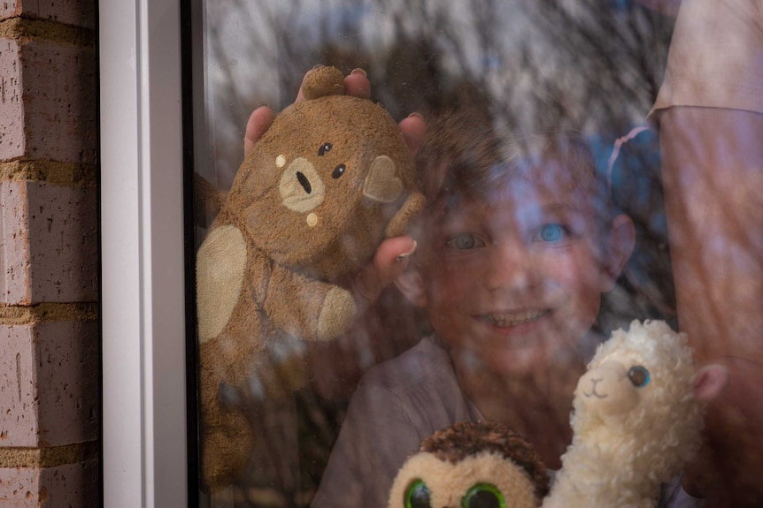 Seven-year-old James Pym is holding a teddy bear up to his window