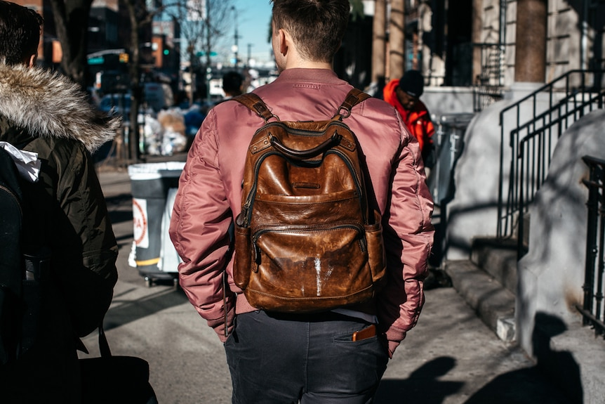 A man in New York wears a brown leather backpack.