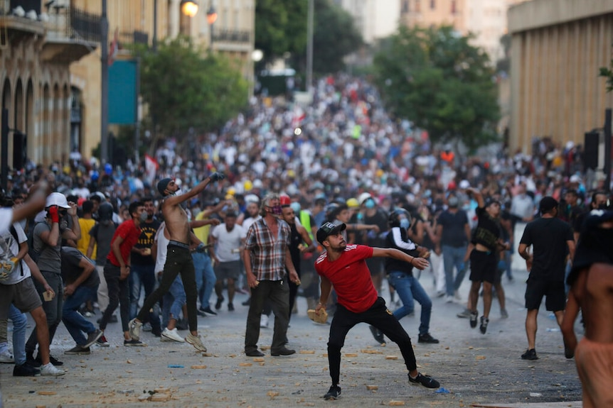 People throw stones during anti-government protest following Tuesday's massive explosion which devastated Beirut.