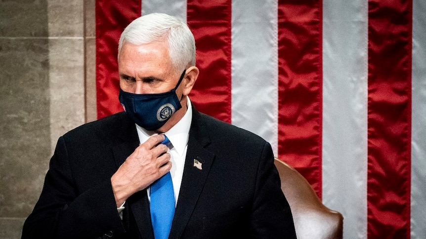 Mike Pence, wearing a mask with the seal of VP on it, stands in front of a US flag