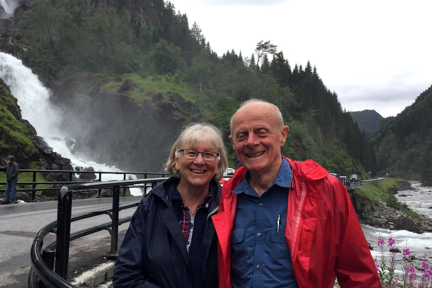 Julie and Jeff Wicks stand smiling in front of a waterfall. Behind them are forest covered mountains.