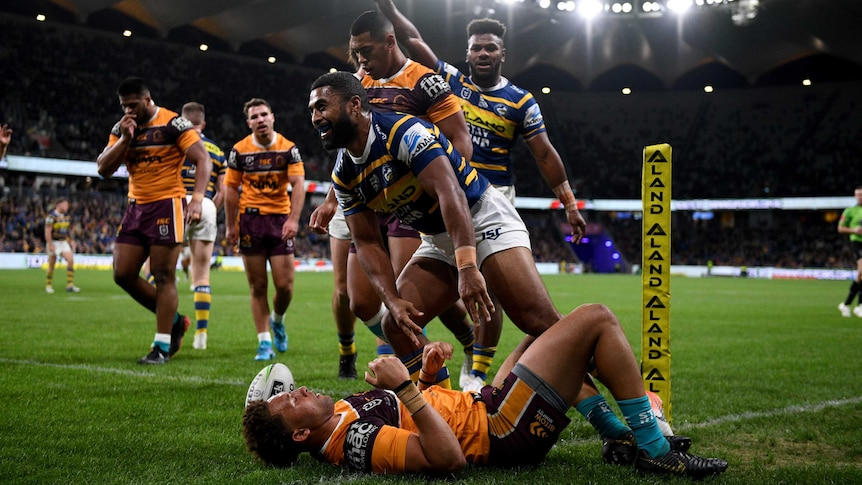 An NRL player stands up, gesturing after scoring a try, surrounded by opposition players.
