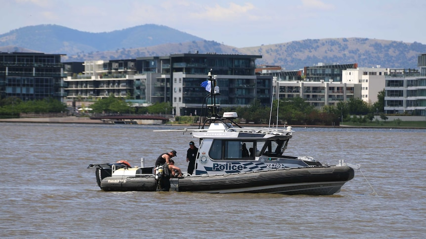 Police diver climbing into a boat on the water