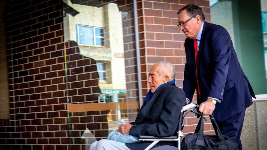 An old man is pushed along outside a court by another man